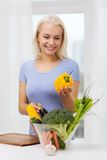 Smiling young woman cooking vegetables at home Stock Image