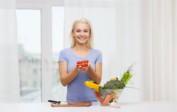 Smiling young woman cooking vegetables at home Royalty Free Stock Photos