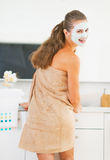 Smiling young woman with cosmetic mask on face in bathroom Royalty Free Stock Photos