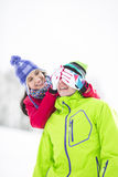 Smiling young woman covering man's eyes in winter Royalty Free Stock Images