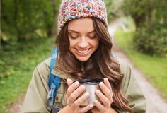 Smiling young woman with cup and backpack hiking Stock Images