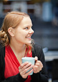 Smiling young woman with cup of chocomilk. Pretty young woman holds a cup of hot drink in a restaurant outdoors Royalty Free Stock Photo