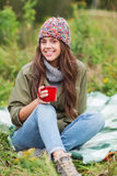 Smiling young woman with cup sitting in camping Royalty Free Stock Photography
