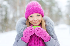 Smiling young woman with cup in winter forest Royalty Free Stock Photo