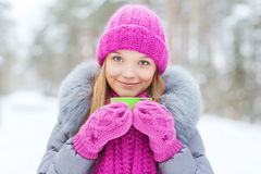 Smiling young woman with cup in winter forest Royalty Free Stock Photography