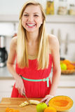 Smiling young woman cutting banana in kitchen Stock Photos
