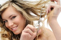 Smiling young woman cutting hair Royalty Free Stock Photo