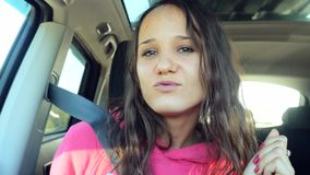Smiling young woman dancing and taking selfie picture with smart phone camera in car. 3840x2160 stock footage