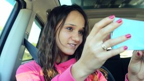 Smiling young woman dancing and taking selfie picture with smart phone camera in the car. 3840x2160 stock video