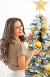 Smiling young woman decorating christmas tree Stock Images