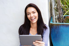 Smiling young woman with a digital tablet Stock Photography