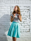 Smiling young woman with a disposable coffee cup Stock Photos