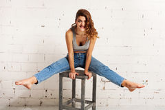 Smiling young woman doing acrobatics on a chair. White brick wall, not  Stock Photos