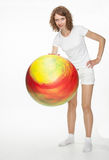 Smiling young woman doing exercises with big fitball. On white background Royalty Free Stock Photography