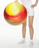 Smiling young woman doing exercises with big fitball. On white background Royalty Free Stock Photo
