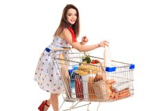 Smiling young woman doing grocery shopping at the supermarket, she is putting a milk bottle in the cart Stock Photo