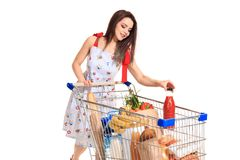 Smiling young woman doing grocery shopping at the supermarket, she is putting a tomato juice bottle in the cart Stock Photography