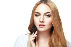 Smiling young woman doing make up Stock Photography
