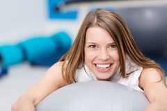 Smiling young woman doing pilates exercises Stock Photos