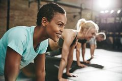 Smiling young woman doing pushups in a gym exercise class