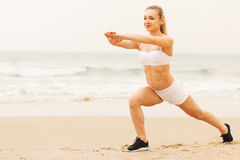 Smiling young woman doing stretching exercise. Royalty Free Stock Image