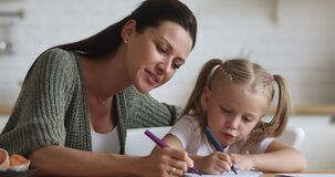 Smiling young woman drawing with little daughter.