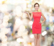 Smiling young woman in dress holding something Royalty Free Stock Images