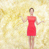 Smiling young woman in dress holding something Royalty Free Stock Image