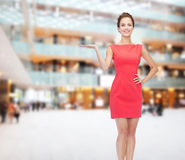 Smiling young woman in dress holding something Stock Photo