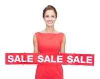 Smiling young woman in dress with red sale sign Stock Photo