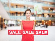 Smiling young woman in dress with red sale sign Royalty Free Stock Photo
