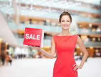 Smiling young woman in dress with red sale sign Royalty Free Stock Image