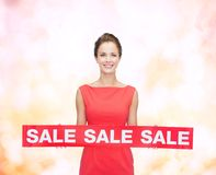 Smiling young woman in dress with red sale sign Stock Photos