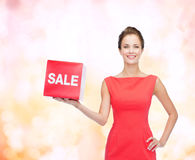 Smiling young woman in dress with red sale sign Stock Images