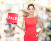 Smiling young woman in dress with red sale sign Stock Photography