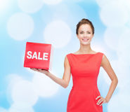 Smiling young woman in dress with red sale sign Royalty Free Stock Photos