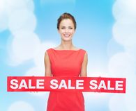 Smiling young woman in dress with red sale sign Royalty Free Stock Images