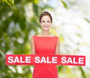 Smiling young woman in dress with red sale sign Royalty Free Stock Photography
