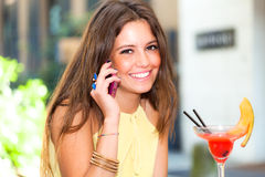Smiling young woman drinking a cocktail Royalty Free Stock Photos