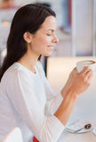 Smiling young woman drinking coffee at cafe Stock Image