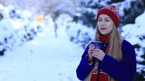 Smiling young woman drinking coffee in cold winter stock footage
