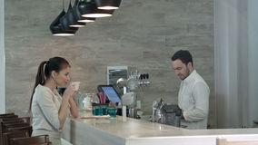 Smiling young woman drinking coffee at the counter and talking to the bartender stock footage