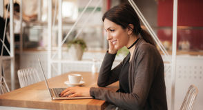 Smiling young woman drinking a coffee and surfing on internet Royalty Free Stock Images