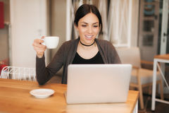 Smiling young woman drinking a coffee and surfing on internet Stock Images