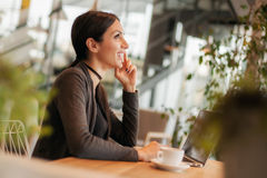 Smiling young woman drinking a coffee and surfing on internet Royalty Free Stock Image