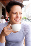 Smiling young woman drinking cup of coffee at cafe Stock Photo