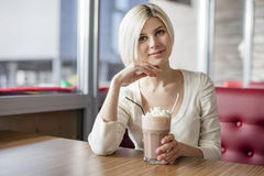 Smiling young woman drinking hot chocolate with cream at cafe Stock Photo