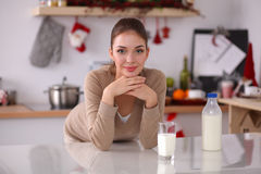 Smiling young woman drinking milk, standing in the Stock Images
