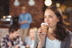 Smiling young woman drinking from take-away cup. Smiling young women drinking from take-away cup in front of her friends at coffee shop Royalty Free Stock Images