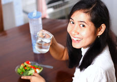 Smiling young woman drinking water with salad on table Royalty Free Stock Images